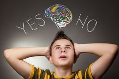 Young boy looking up at Yes and No words. And human brain Royalty Free Stock Photography