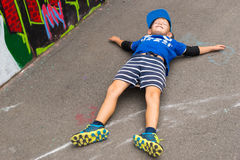 Young Boy Lying on Back in Lot near Graffiti Wall Stock Photography