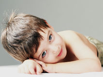 A young boy lying in a bed smiling. A  young boy lying in a bed smiling Stock Photography