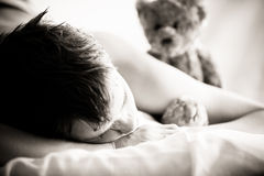 Young Boy Lying on Bed with Teddy Bear Royalty Free Stock Photography