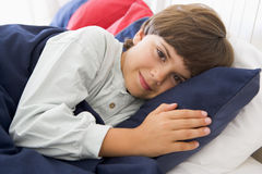 Young Boy Lying Down In His Bed Royalty Free Stock Photography