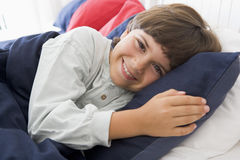 Young Boy Lying Down In His Bed Royalty Free Stock Photos