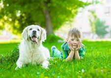 Young boy lying with golden retriever dog on green grass.  royalty free stock photo