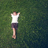 Young boy lying in the grass Stock Photography