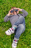 Young boy lying on his back with binoculars Stock Photo