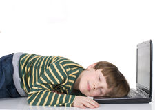 Young boy lying on laptop Royalty Free Stock Photos