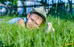 Young Boy Lying in Long Grass with Fuzzy Chick Royalty Free Stock Photos