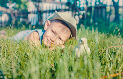 Young Boy Lying in Long Grass with Fuzzy Chick Stock Image