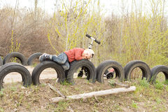 Young boy lying on old tyres Stock Images