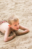 Young Boy Lying on a Sandy Beach Royalty Free Stock Photo