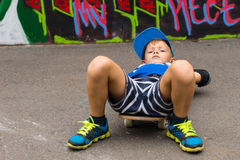 Young Boy Lying on Skateboard in Paved Lot Stock Image