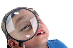 Young boy with magnifying glass. Young boy playing with a magnifying glass royalty free stock photo