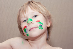 Young boy make selfie with face covered in colourful paint. Royalty Free Stock Image
