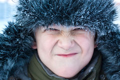 Young boy making face. The portrait of grimacing young boy in winter outerwear with artificial fur, close-up Stock Photography