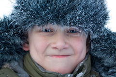 Young boy making face. The portrait of grimacing young boy in winter outerwear with artificial fur, close-up Royalty Free Stock Image
