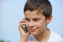 Young boy making a phonecall. A young boy outside is making a phonecall with his cellphone Stock Photo