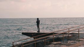 Young boy making photo of stormy sea. Man takes picture of ocean. Lonely boy standing at promenade.  stock video