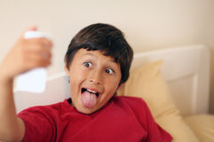 Young boy making selfie pictures. With smart phone - with shallow depth of field Stock Images