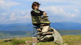 Young boy making a wish. Young boy meditating on a mountain top Stock Photo