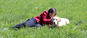 Young boy on the meadow in the mountains with his labrador dog Royalty Free Stock Photography