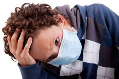 Young boy with a medical mask, and hand on head Stock Photo