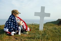 A young boy in a military cap, covered by the flag of the united states sitting on the grave of his deceased father. May 27th. Memorial day royalty free stock photos