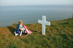 A young boy in a military cap, covered by the flag of the united states sitting on the grave of his deceased father. May 27th. Memorial day royalty free stock image