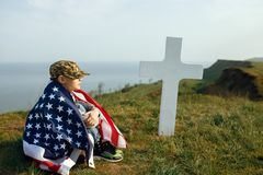 A young boy in a military cap, covered by the flag of the united states sitting on the grave of his deceased father. May 27th. Memorial day stock image