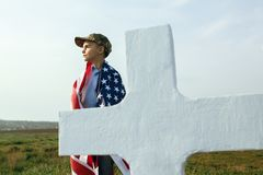 Young boy in a military cap at his father`s grave on memorial day.  stock photography