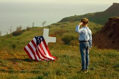 A young boy in a military cap salutes his father`s grave on memorial day.  stock photos