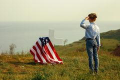 A young boy in a military cap salutes his father`s grave on memorial day.  royalty free stock photos