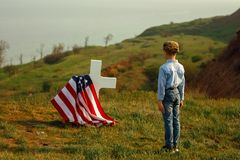 A young boy in a military cap salutes his father`s grave on memorial day.  royalty free stock photo