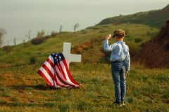 A young boy in a military cap salutes his father`s grave on memorial day.  stock photography