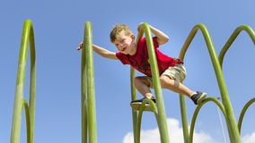 Brave young boy cimbing on playframe. royalty free stock image