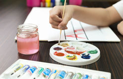 Young boy  mixes paint of different colors on palette Royalty Free Stock Photography