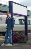 Young boy on mobile phone. An image of a young teenage boy talkuing on a mobile phone at a train station, leaning against a sign post stock photography