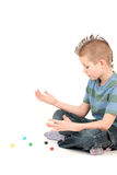 Young boy with mohawk. Portrait of young boy with mohawk playing with dice, studio shot Royalty Free Stock Photos