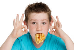 Young Boy with Mouth Full of Chips. Young boy with a mouth full of chips fries. Isolated on white background Stock Photo