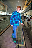 Young boy on a moving staircase inside the airport Royalty Free Stock Images