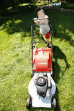 Young boy mowing grass Stock Image