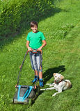 Young boy mowing the lawn accompanied by his labrador doggie. Young boy mowing the lawn together with his labrador dog in summer stock image