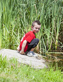 Young boy near pond Stock Images
