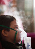 Young boy with nebuliser. Young boy wearing mask of nebuliser with steam Royalty Free Stock Photo