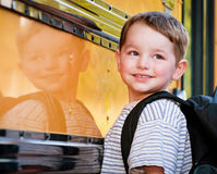 Young boy with nervous smile waits to board bus Royalty Free Stock Photo