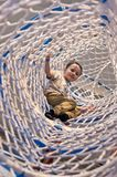 Boy in net sleeve of amusement park climbing facility Stock Photos