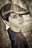 Young boy with newsboy cap playing detective. Young boy with newsboy cap leaning on a tree and playing detective. Vintage style photo Royalty Free Stock Images