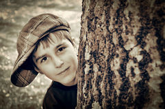 Young boy with newsboy cap playing detective. Young boy with newsboy cap sneaking behind a tree and playing detective. Vintage style photo Royalty Free Stock Photography