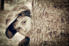 Young boy with newsboy cap playing detective. Young boy with newsboy cap sneaking behind a tree and playing detective. Vintage style photo Stock Photos