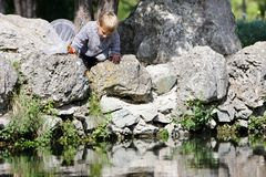 Young Boy On Rocks And Looking Into Water Royalty Free Stock Photos