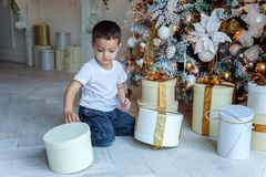 Young boy opens a gift under a Christmas tree Stock Photo